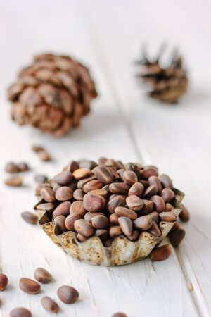 Pine or cedar nuts in a metalic bowl on the white wooden table.