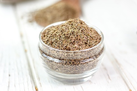 Cumin or caraway spice in a glass jar over white wooden background.