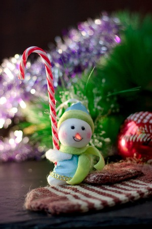 Toy snowman holding christmas candy cane in hands.