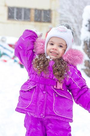 Winter activity - little girl playing snowballs. Stock Photo