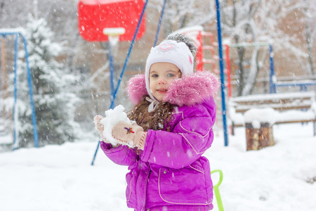 Little kid girl playing snowballs on winter morning.