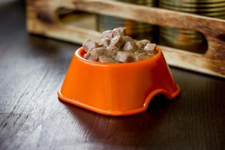 Ingeblikt voedsel voor huisdieren in een oranje plastic kom.