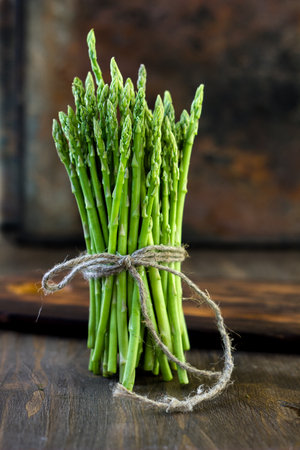 Hip of asparagus standing on wooden board.
