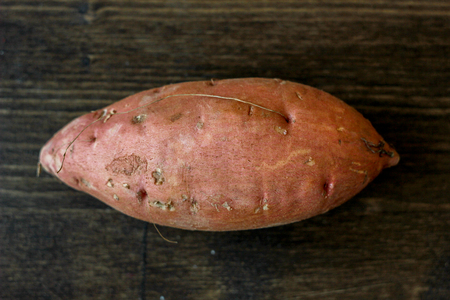 Sweet potatoes on black wooden table.