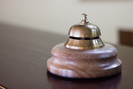 Service bell in a hotel reception for concierge alarm on desk. Stock Photo