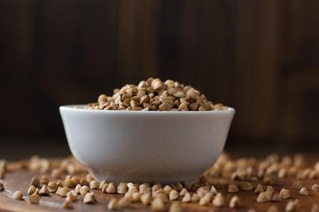 木製のテーブルの上にセラミックボウル上のそばの穀物。