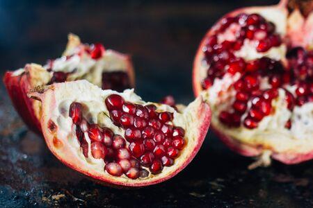 Quarter of pomegranate fruit on black rustic surface.