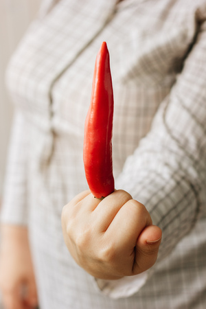 Fuck you sybmol - woman holding chilli pepper like middle finger