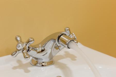 Bidet mixer showering with water on modern bathroom.
