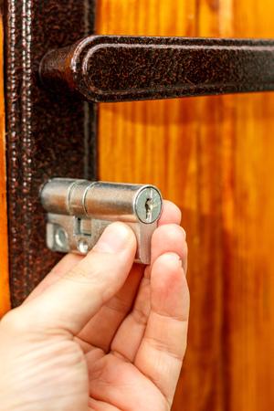 Locksmith installs new door lock into wooden door Stock Photo - 94010467 & Locksmith Installs New Door Lock Into Wooden Door Stock Photo ...