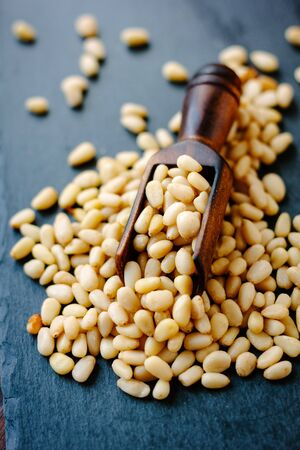 Natural organic pine nuts on a black slate with scoop