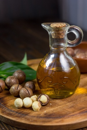 Natural macadamia oil in a glass bottle with macadamia nuts on wooden board