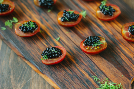 Red cherry tomatoes and black caviar appetizers on wooden board Stock Photo