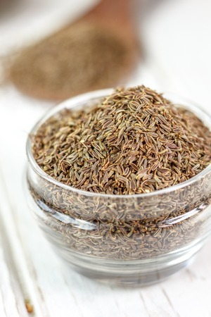 Cumin or caraway spice in a glass jar over white wooden background