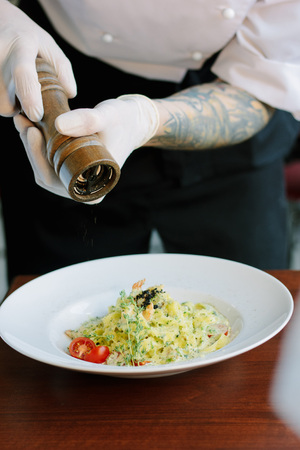 Chief hands dressing italian fettuccine pasta with pepper mill