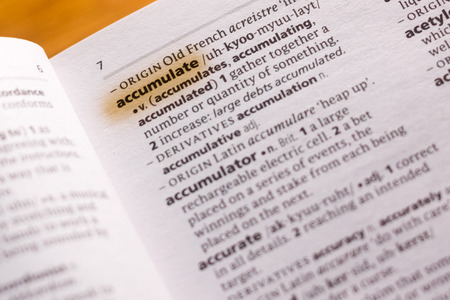 The word or phrase Accumulate in a dictionary highlighted with marker.