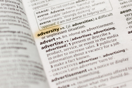 The word or phrase Adversity in a dictionary highlighted with marker. 版權商用圖片