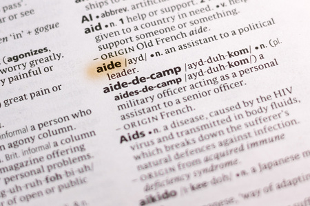 The word or phrase Aide in a dictionary highlighted with marker.