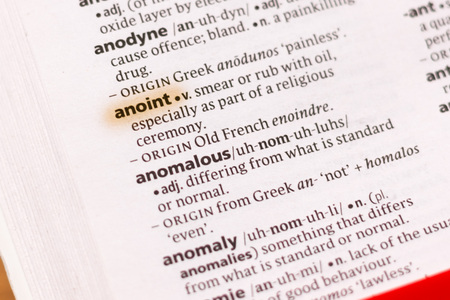 The word or phrase Anoint in a dictionary highlighted with marker.