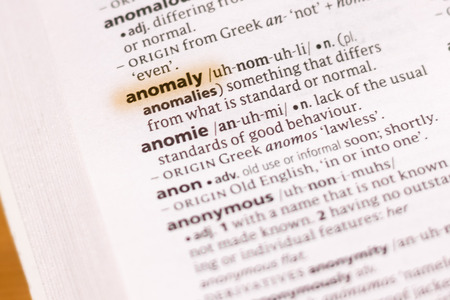The word or phrase Anomaly in a dictionary highlighted with marker.