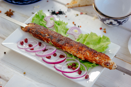 Meat kebab on sckewer, chiken kebab on white plate, great image for your needs.