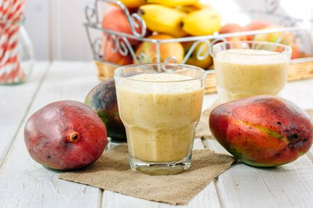 Glass with fresh mango smoothie over white wooden table Standard-Bild - 124720275