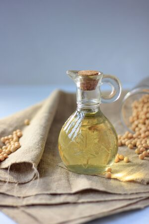 Natural soybean oil in glass bottle with soy beans near it Standard-Bild - 124720287