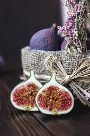 Basket of fig fruits with the halves one on a table Standard-Bild - 124720293
