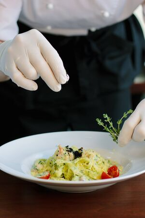Chief dressing pasta with black truffle and herbs 写真素材