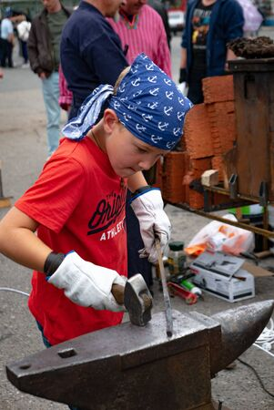 Ryazan, Russia - July 27, 2019: Kid boy works with metal detail on blacksmith festival.