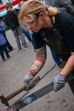 Ryazan, Russia - July 27, 2019: Woman blacksmith works with metal on the forge festival 新聞圖片