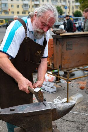 Ryazan, Russia - July 27, 2019: Old blacksmith with hammer on street festival.