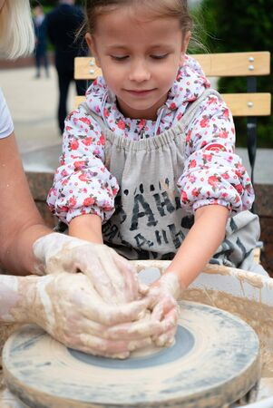 Ryazan, Russia - July 27, 2019: Kid during pottery master-class on street festival 新聞圖片