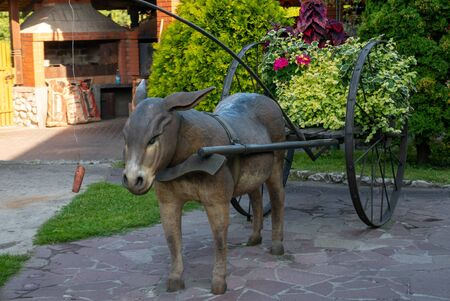 Metal donkey in a park carring plants.