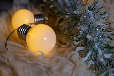 Christmas garland lights on a white carpet.