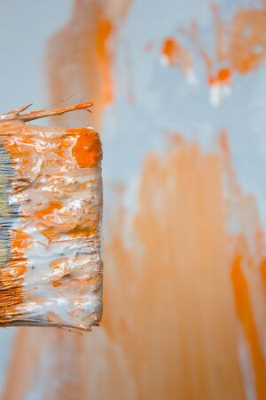 Brush with orange and white paint as renovation and creation.