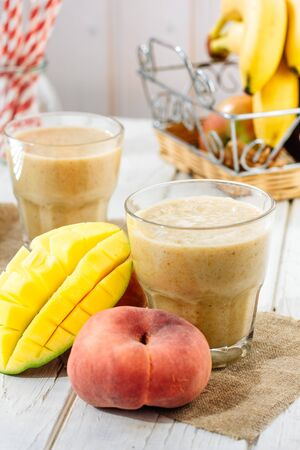 Mango and peach smoothie on wooden table with ingredients 写真素材