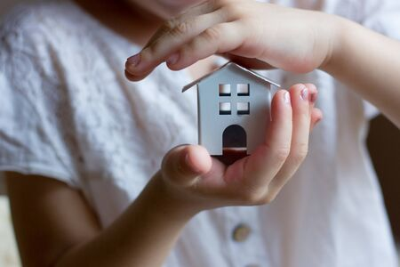 Little girl holding small house in hands.