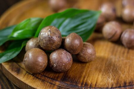 Fresh and ripe macadamiya nuts on the wooden board