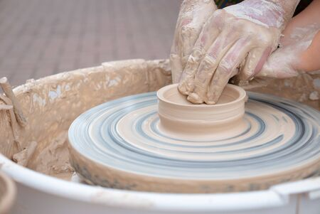 Hands forming clay on the pottery wheel.