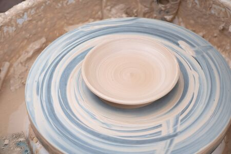 Clay plate rotating on the pottery wheel. 写真素材