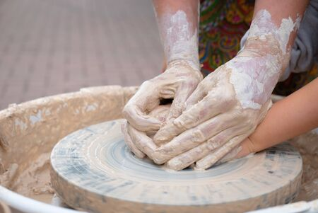 Hands forming clay on the pottery wheel. Stock fotó