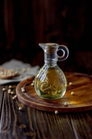 Soy bean oil in glass bottle with soybeans around it
