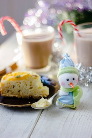 Christmas decoration at white table - snowman with piece of pie in spoon Stockfoto
