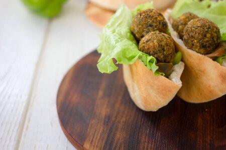 Falafel balls inside pita bread with lettuce and vegetables
