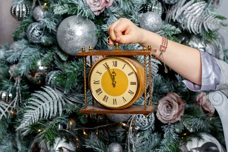 Christmas and new year concept - hand holding retro clock with the midnight time
