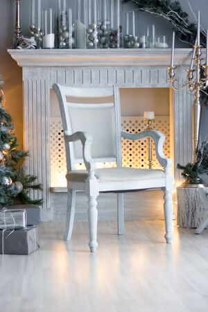 Christmas decoration - room with beautiful chair, fireplace and christmas tree.