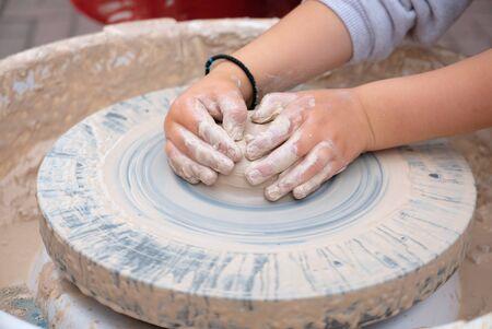 Kid hands forming clay on a pottery wheel 版權商用圖片