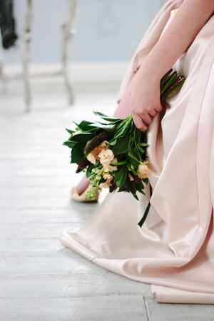 Woman in beautiful dress holding flower bouquet in hands