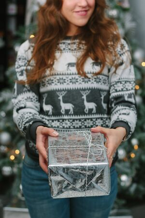 Girl giving a christmas gift in a silver box to you - christmas and new year concept. 版權商用圖片